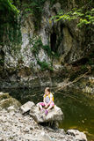 Pensive little girl sitting on a big rock by a small pond Stock Images