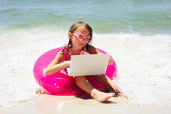 Pensive little girl sitting with laptop on beach Royalty Free Stock Images