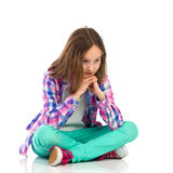 Pensive little girl sitting with legs crossed Stock Photo