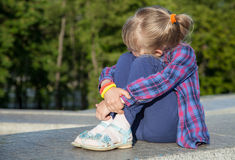 Pensive little girl sitting on the parapet wall Royalty Free Stock Photo