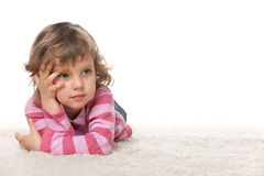 Pensive little girl on the white carpet royalty free stock images