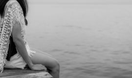 Pensive lonely adult Asian woman. Back view of woman with sad feeling in black and white scene at the sea. Depressed and stressed. Girl sit on wooden pier at stock photo