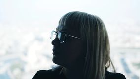 The pensive look of the girl. Girl with glasses on the background of a bright window. stock video