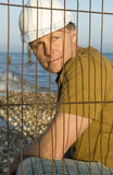 Pensive looking construction worker. A portrait of a pensive looking construction worker wearing a hard hat and looking through a steel wire fence Royalty Free Stock Photos
