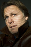 Pensive looking man. A colour portrait photo of a pensive and anxious looking man in his forties wearing a leather coat with the colllar up stock photos
