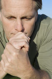 Pensive looking man. A pensive looking man is laying on his front and looking anxious Stock Photography