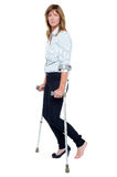 Pensive looking woman using crutches to walk Royalty Free Stock Image