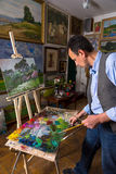 Pensive male artist mixing colors in a gallery Royalty Free Stock Image
