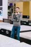 Pensive male customer in eyeglasses choosing orthopedic mattress. In furniture shop stock photo