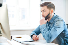 Pensive male designer thinking and making blueprints using pen tablet. Pensive attractive bearded male designer in jeans shirt thinking and making blueprints Stock Photos