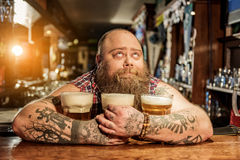 Pensive male embracing mugs of alcohol beverage Stock Photo