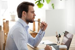 Pensive male employee think of problem solution. Pensive millennial office worker think of problem solution working at laptop, thoughtful male employee pondering royalty free stock photography