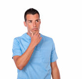 Pensive male nurse on blue uniform standing Stock Photo