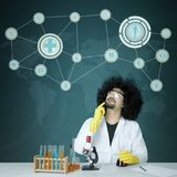 Pensive male scientist with virtual screen background. Photo of pensive male scientist looking up while doing chemical research. Shot with virtual screen Royalty Free Stock Images
