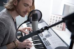 Pensive male singer performing melody on synthesizer. E view of thoughtful young man singing into the microphone while playing electronic piano Stock Image