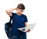 Pensive male student holding laptop. Isolated on a white background Royalty Free Stock Photos