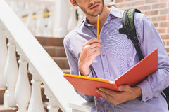 Pensive male student studying with concentration. Thoughtful young man is learning subject outdoors. He is standing and touching pencil to chin. Guy is holding Stock Photography