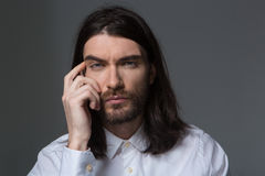 Pensive man with beard and long hair looking at camera Royalty Free Stock Photography