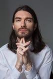 Pensive man with beard and long hair looking at camera. Portrait of a pensive man with beard and long hair looking at camera over gray background Stock Photos
