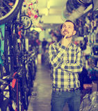 Pensive man in bicycle shop chooses for himself sports bike Royalty Free Stock Images