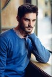 Pensive man with blue sweater with lost look near a window Stock Photo