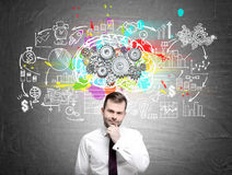 Pensive man and brain with gears, blackboard. Portrait of a doubtful bearded man standing near a brain with gears sketch drawn on a blackboard with a startup Stock Photography