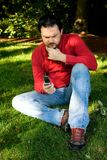 Pensive Man with Cellphone in Park Stock Images