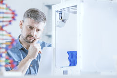 Pensive man and 3d printer. Pensive man working at laboratory, using 3d printer royalty free stock photo