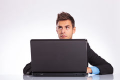 Pensive man at desk with laptop Royalty Free Stock Image