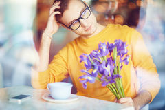 Pensive Man with Flowers Waiting for Date Royalty Free Stock Photos