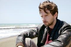 Pensive man in front of the sea thinking feeling sad medium shot Stock Photography