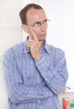 Pensive man with glasses touching chin. Stock Photo