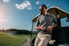 pensive man with golf ball in hand looking away while standing