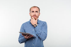 Pensive man holding tablet computer and looking up Stock Images