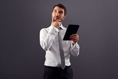 Pensive man holding tablet pc Stock Photos