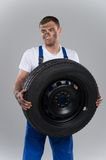 Pensive man holding tire on grey background. Royalty Free Stock Photos