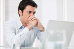 Pensive man at laptop Stock Images