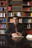 Pensive Man At Library Desk Royalty Free Stock Photos