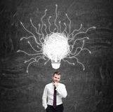 Pensive man and light bulb with arrows Stock Photo