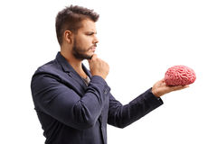 Pensive man looking at a brain model Royalty Free Stock Images