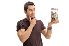 Pensive man looking at a jar filled with money. Isolated on white background Royalty Free Stock Photos
