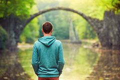 Pensive man is looking at the old bridge. Pensive young man on the pond bank. - Amazing place in Germany. Rakotzbrucke also known as Devils Bridge in Kromlau Royalty Free Stock Image