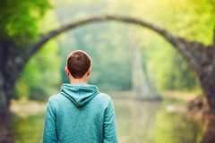 Pensive man is looking at the old bridge. Pensive young man on the pond bank. - Amazing place in Germany. Rakotzbrucke also known as Devils Bridge in Kromlau Royalty Free Stock Photo