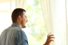 Pensive man looking through a window. Single pensive man looking outdoors through a window at home or hotel stock photos