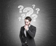 Pensive man near question mark Stock Photo