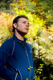 Pensive Man Outdoors. Portrait of a pensive young man standing outdoors in a wooded area, looking up toward the sky royalty free stock images