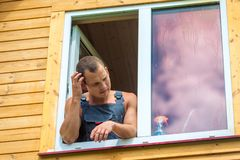 Pensive man in overalls reflects on washing the window. In the house royalty free stock image