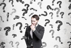 Pensive man, question marks falling Royalty Free Stock Photos