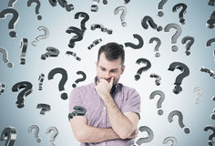 Pensive man and question marks Stock Photo