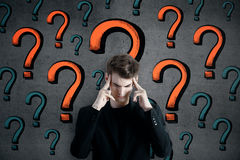 Pensive man with question marks Stock Photography